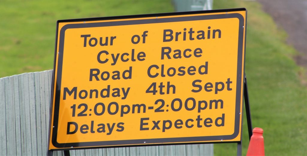 Coastal Road Trip, Tour of Britain Cycle Race, Bamburgh, Sign, Delays Expected